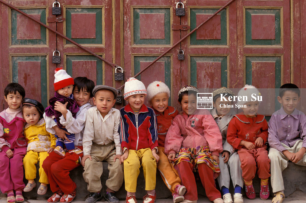 Uighur children sitting by gate Xinjiang Province Silk Road China