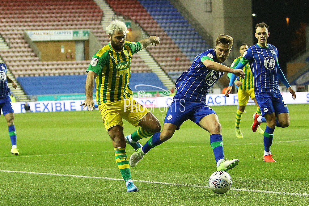 West Bromwich Albion forward Charlie Austin (15) and Wigan Athletic midfielder Michael Jacobs (17) during the EFL Sky Bet Championship match between Wigan Athletic and West Bromwich Albion at the DW Stadium, Wigan, England on 11 December 2019.