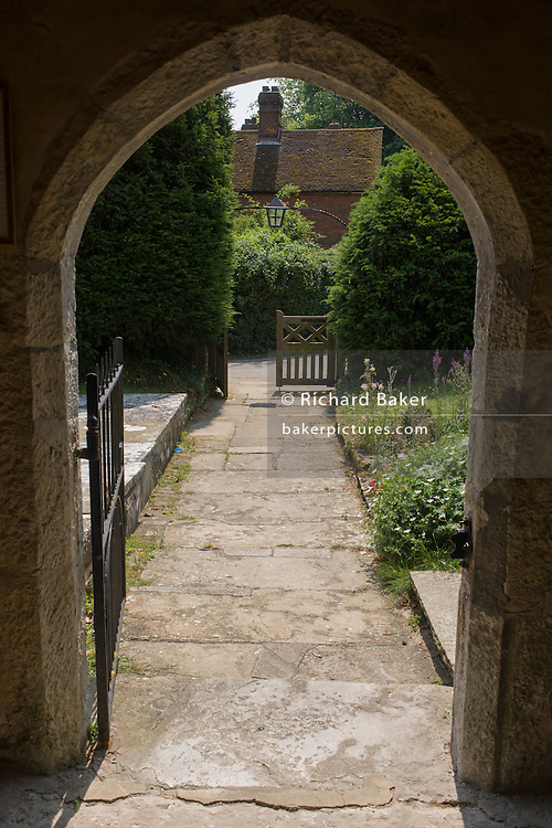 Looking down the path of a churchyard towards an open gate and a village cottage in West Peckham, Kent, England UK
