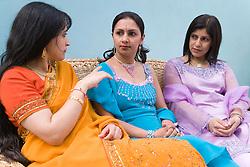 Three women wearing traditional Asian dress sitting talking,
