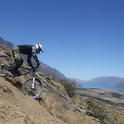 Matthew Wood from Dunedin in action during the New Zealand South Island Downhill Cup Mountain Bike series held on The Remarkables face with a stunning backdrop of the Wakatipu Basin. 150 riders took part in the two day event. Queenstown, Otago, New Zealand. 9th January 2012. Photo Tim Clayton