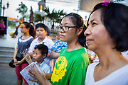 27 JANUARY 2013 - BANGKOK, THAILAND:   Women pray as a deity is carried into the temple for Thaipusam at Dhevasathan (the Brahmin Shrines) on Dinso Rd in Bangkok. Thaipusam is a Hindu festival celebrated primarily by the Tamil community in South East Asia on the full moon in the Tamil month of Thai (Jan/Feb). Pusam refers to a star that is at its highest point during the festival. The festival commemorates both the birthday of the Hindu god Murugan, son of Shiva and Parvati, and the occasion when Parvati gave Murugan a vel (a lance) so he could vanquish the evil demon Soorapadman. The holy day is celebrated by Brahmins in Thailand. Brahmanism was the court religion before Buddhism came to Thailand and before the foundation of Sukhothai. Both religions are combined in the Thai way of life and its customs and ceremonies.       PHOTO BY JACK KURTZ