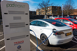 Tesla electric car charging at free Pod Point charging station in Tesco supermarket, UK, United Kingdom