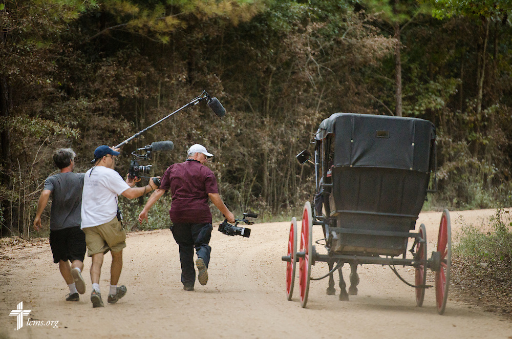 (L-R) Audio Supervisor Mike Budzik, Director of Photography Ben DeSousa and Cameraman Al Dowbnia run with a horse and buggy for a scene on the final day of filming for 'The First Rosa' documentary on Thursday, September 25, 2014, near Selma, Ala. LCMS Communications/Erik M. Lunsford