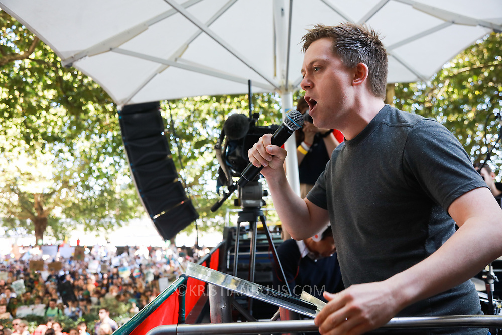 Tens of thousands took to the streets in Central London taking part in the the Global Climate Strike, September 20th 2019, London, United Kingdom.  Owen Jones, journalist and political activist for social and climate justice  adresses the crowd. The day of strike for the climate was a global event with millions taking part across the globe. The strike was inspired by Greta Thunberg, a Swedish school girl who started the first school strike for the climate. Her action inspired school children across the world to go on strike demanding radical climate change policies to save their future. On September 20th adults aand children alike went out on strike to demand radical political change and climate justice. The day included speeches and a march through central London.