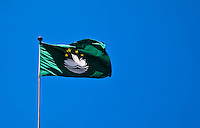 Macau flag fluttering in the wind against a blue sky.