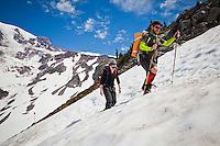 A man and woman make their way up Mount Rainier on the Skyline trail, Washington, USA.