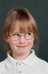 Portrait of young girl wearing glasses looking cheeky,