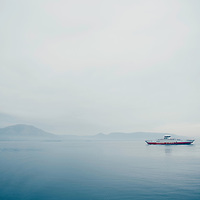 A small ferry crossing calm waters in Greece on a summers day