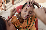 Mera (R), ( 19 years) is readying herself for the Wedding and is receiving threading, an extremely old skill that involves using a piece of thread to remove the hair from the eyebrows (or elsewhere). Varanasi, India.