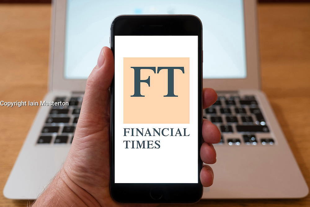 Using iPhone smartphone to display homepage of Financial Times , FT, newspaper