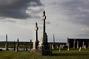 Low angle view of numerous Gravestones, with the River Shannon and Temple Connor, 1010, by Cathal O'Conor, in the background, Clonmacnoise, County Offaly, Ireland, in the evening. Temple Connor, restored in the 20th century, is the only active church at Clonmacnoise. It has been used by the Church of Ireland since the 18th century. Clonmacnoise was founded by St Ciaran, with the help of Diarmait Ui Cerbaill, Ireland's first Christian King. The site presents the largest collection of Early Christian graveslabs in Western Europe. Picture by Manuel Cohen