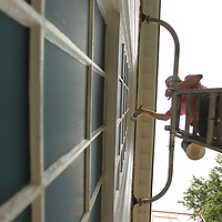 Brandon Warner of Willie's Painting Service works to paint the trim and windows at First Presbyterian Church in Corinth on Shilioh Road Tuesday afternoon. The work that is being done is part of their annual maintance to the church.