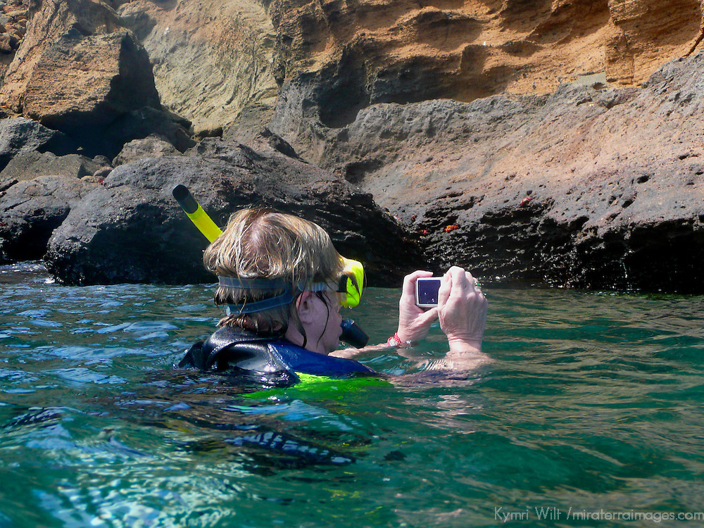 South America, Ecuador, Galapagos Islands, Bartholomew Island. A snorkeller in the bay at Pinnacle Rock.