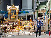 18 AUGUST 2015 - BANGKOK, THAILAND: A man stands in front of Erawan Shrine Tuesday. Litter and debris from an explosion at the shrine are still on the ground. An explosion at Erawan Shrine, a popular tourist attraction and important religious shrine in the heart of the Bangkok shopping district, killed at least 20 people and injured more than 120 others, including foreign tourists, during the Monday evening rush hour. Twelve of the dead were killed at the scene. Thai police said an Improvised Explosive Device (IED) was detonated at 18.55. Police said the bomb was made of more than six pounds of explosives stuffed in a pipe and wrapped with white cloth. Its destructive radius was estimated at 100 meters.     PHOTO BY JACK KURTZ