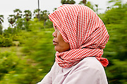 "01 JULY 2006 - PHNOM PENH, CAMBODIA: A woman rides the ""Bamboo Train"" in rural Cambodia. The ""bamboo trains"" run along the government tracks in rural Cambodia. Bamboo mats are fitted over wheels which on the rails. The contraption is powered by a either a motorcycle or lawn mower engine. The Cambodian government would like to get rid of the bamboo trains, but with only passenger train in the country, that runs only one day a week, the bamboo trains meet a need the government trains do not. While much of Cambodia's infrastructure has been rebuilt since the wars which tore the country apart in the late 1980s, the train system is still in disrepair. There is now only one passenger train in the country. It runs from Phnom Penh to the provincial capitol Battambang and it runs only one day a week. It takes 12 hours to complete the 190 mile journey.  PHOTO BY JACK KURTZ"