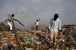 Workers at a local garbage dump, who scavenge for trash that they can sell, try to put out a fire so they can continue working.  Local NGOs say that there is a huge problem with TB among the workers in the dumping ground, as well as the families that live near it, owing it poor nutrition and hygiene, which can make them more susceptible to developing active TB.