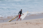 A surfer carries his surfboard, broken in two pieces, into shore.