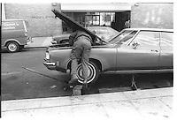 Man repairing a car, NYC, Street photography, 1980.