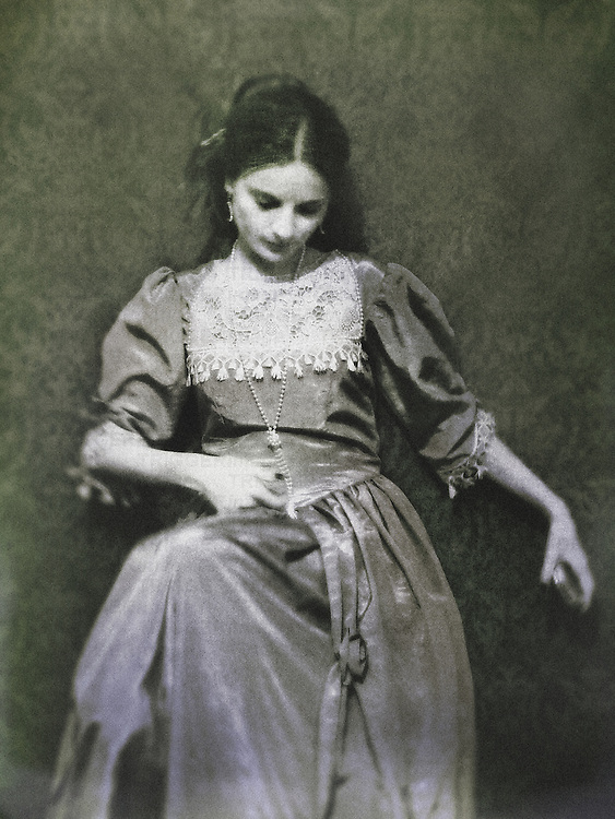 A woman sitting by a decorative wallpaper, with  dark hair and closed eyes, dressed in a historical baroque / victorian gown.