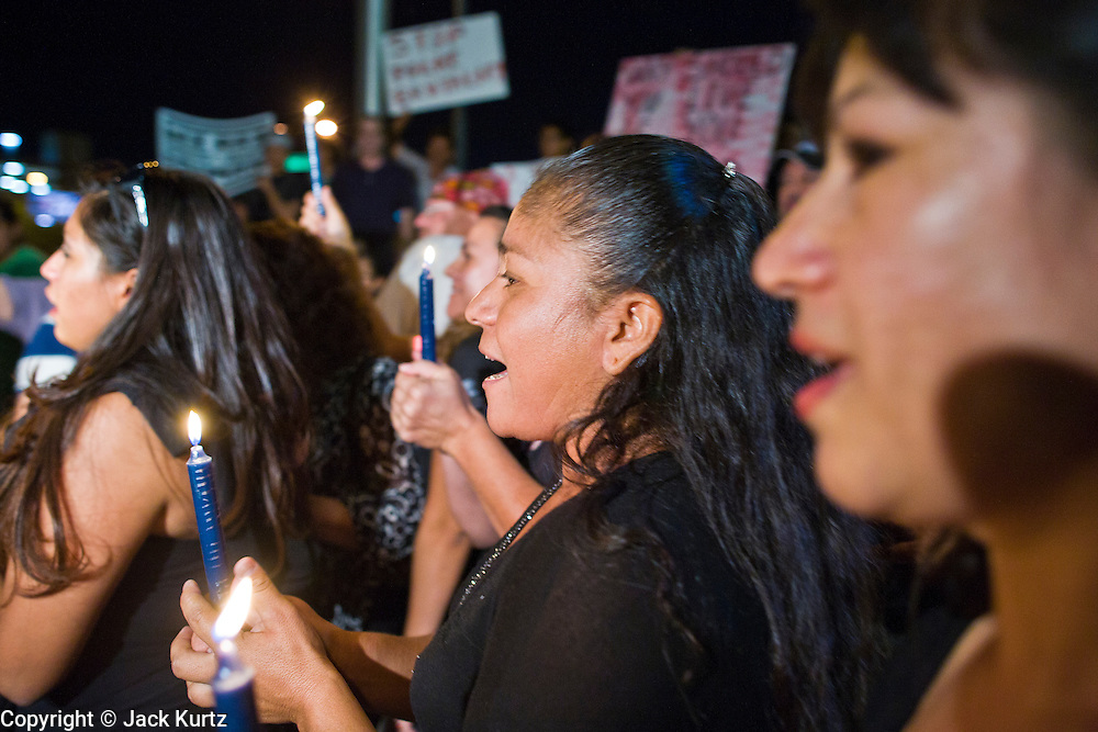 11 OCTOBER 2010 - PHOENIX, AZ:  GEORGINA SANCHEZ, (center) from Phoenix, and others participate in a candle light march around Phoenix police headquarters Monday night. About 300 people gathered at the Phoenix Police Department headquarters building Monday night to protest the shooting of Daniel Rodriguez and his dog. The officers responded to a 911 call made by Rodriguez' mother. A scuffle ensued when they arrived and Phoenix police officer Richard Chrisman shot Rodriguez, who was unarmed, and his dog. Chrisman then allegedly filed a false report about the event. He has been arrested on felony assault charges. The event has angered some in the Latino community and they have held a series of protests at the police headquarters. They want Chrisman charged with murder.    Photo by Jack Kurtz