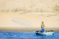 A small-scale fisher throws his cast net from his wooden rowing boat, Sundays River Estuary, Algoa Bay, Eastern Cape, South Africa