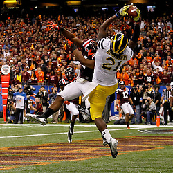 January 3, 2012; New Orleans, LA, USA; Michigan Wolverines wide receiver Junior Hemingway (21) catches a touchdown over Virginia Tech Hokies safety Antone Exum (1) during the third quarter of the Sugar Bowl at the Mercedes-Benz Superdome.  Mandatory Credit: Derick E. Hingle-US PRESSWIRE