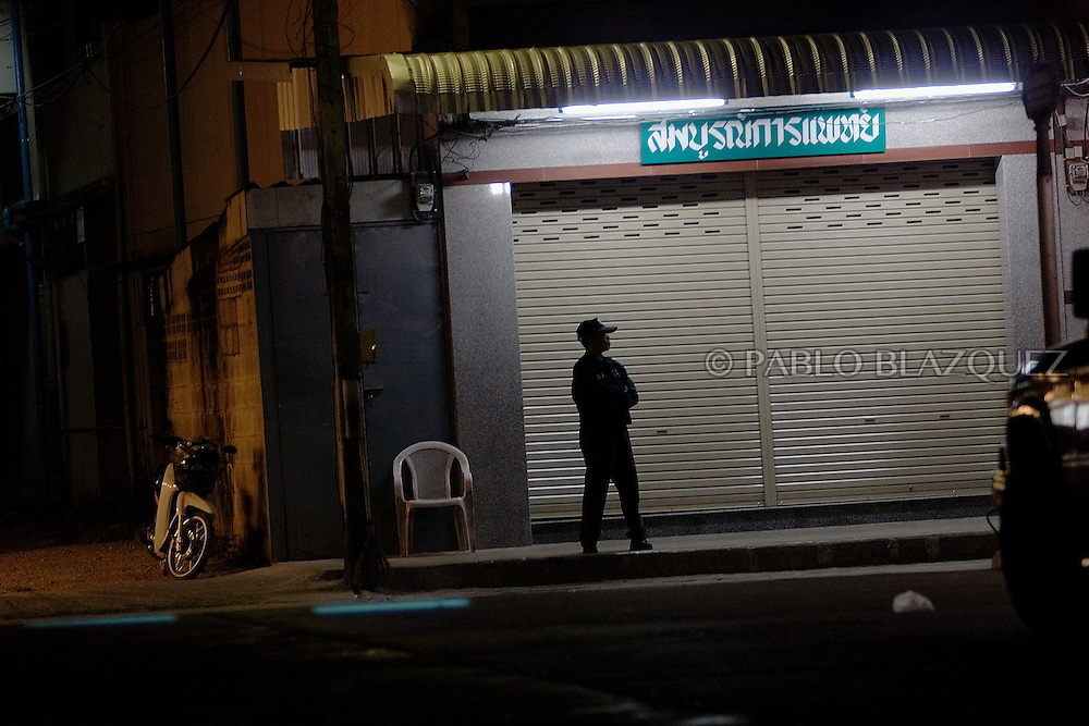 A security man patrolling at night on December 21 of 2006, in Mae Sot, Thailand. Security staff and police patrols and watches the street all night while streets are empty. The border is a hotbed of smuggling gems, drugs or even human beens..Burma has since 1962 been ruled by dictator Burman Regimes. Pro democrats and minority ethnics have since been object of human rights abuses and armed minority groups has appeared bringing a state of Civil War..This situation makes every days people to flee their villages to go to Thailand.