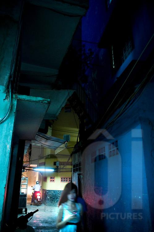 A Vietnamese woman walks through a very narrow alleyway at night, Ho Chi Minh city, Vietnam, Southeast Asia