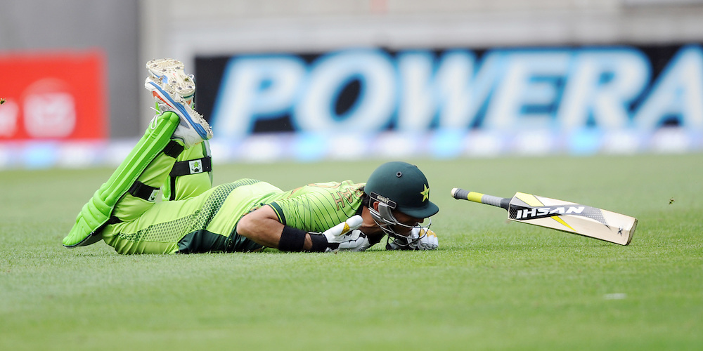 Pakistan's Misbah-ul-Haq losers his bat as he dives in to make his ground against New Zealand in the 1st One Day International cricket match at Westpac Stadium, New Zealand, Saturday, January 31, 2015. Credit:SNPA / Ross Setford