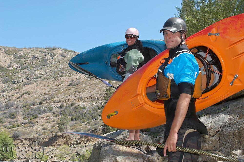 Male and female kayakers on riverbank, portrait