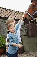 Sister and brother (5-6 7-9) stroking horse outside stable