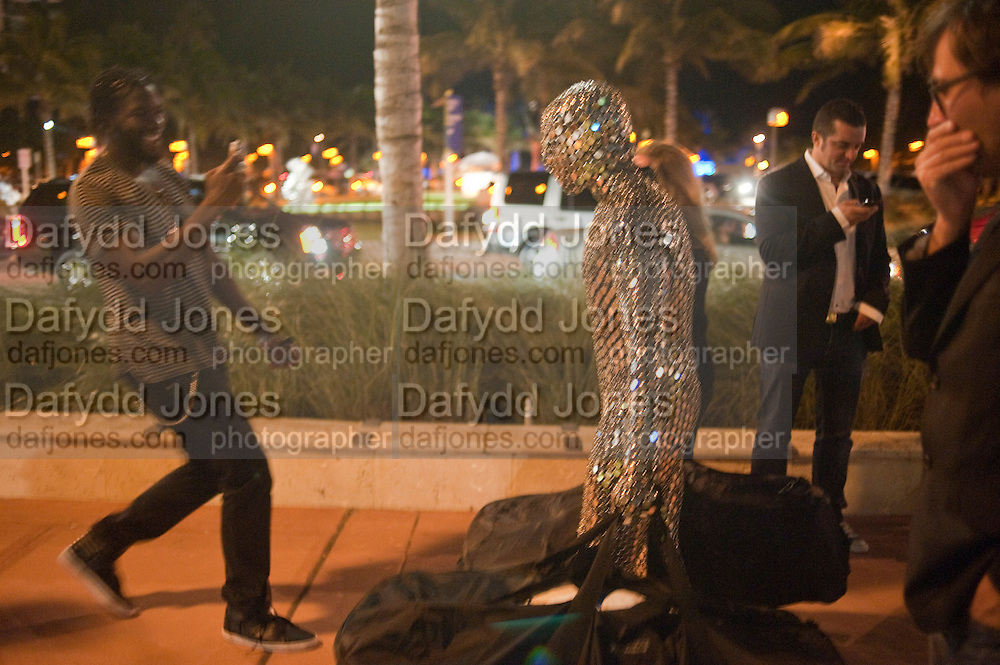 man in silver body suit distributing art basel bags; Art Event in Collins Park  during of Miami Art Basel 2011, Miami Beach. 30 November 2011.