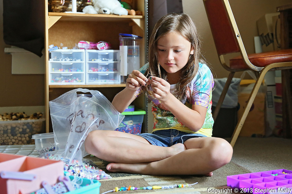 """Raegan Junge, 8, of Keystone works on making a bead bracelet in her """"office"""" at her house in Keystone on Wednesday, July 17, 2013."""
