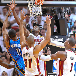 Jun 17, 2012; Miam, FL, USA; Oklahoma City Thunder point guard Russell Westbrook (0) shoots over Miami Heat shooting guard Dwyane Wade (3) and small forward Shane Battier (31) during the third quarter in game three in the 2012 NBA Finals at the American Airlines Arena. Mandatory Credit: Derick E. Hingle-US PRESSWIRE