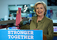 U.S. Democratic presidential nominee Hillary Clinton holds up aat a Donald Trump brand tie made in China during a stop at a local tie company in Denver August 3, 2016. REUTERS/Rick Wilking