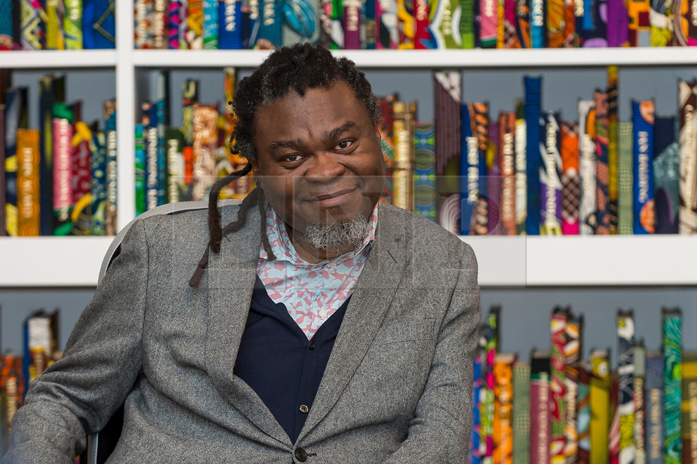 "© Licensed to London News Pictures. 08/04/2019. LONDON, UK.  British-Nigerian artist Yinka Shonibare poses at a photocall with his work ""The British Library"", 2014, which has been acquired by Tate Modern.  Comprising 6,328 books, covered in wax fabric and gold foil, 2,700 books have the names of first or second generation immigrants to Britain on the spine.  Photo credit: Stephen Chung/LNP"