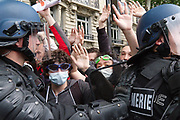 France, Paris, 14 June 2016. National protest against labor reform law project in Paris. While a violent confrontation between dozens of radicals and Riot Police occurs, other Riot Police officers block the head of rally. Protesters show the of non violence.
