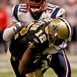 2009 November 30: New England Patriots safety Brandon McGowan (30) knocks New Orleans Saints wide receiver Marques Colston (12) into the endzone for a touchdown in the second half during a 38-17 win by the New Orleans Saints over the New England Patriots at the Louisiana Superdome in New Orleans, Louisiana.