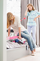 Sisters trying to close suitcase at home