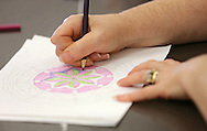 An attendee works on coloring a mandalas during the Retreat & Refresh Stroke Camp at Camp Courageous in Monticello on Saturday, April 20, 2013.