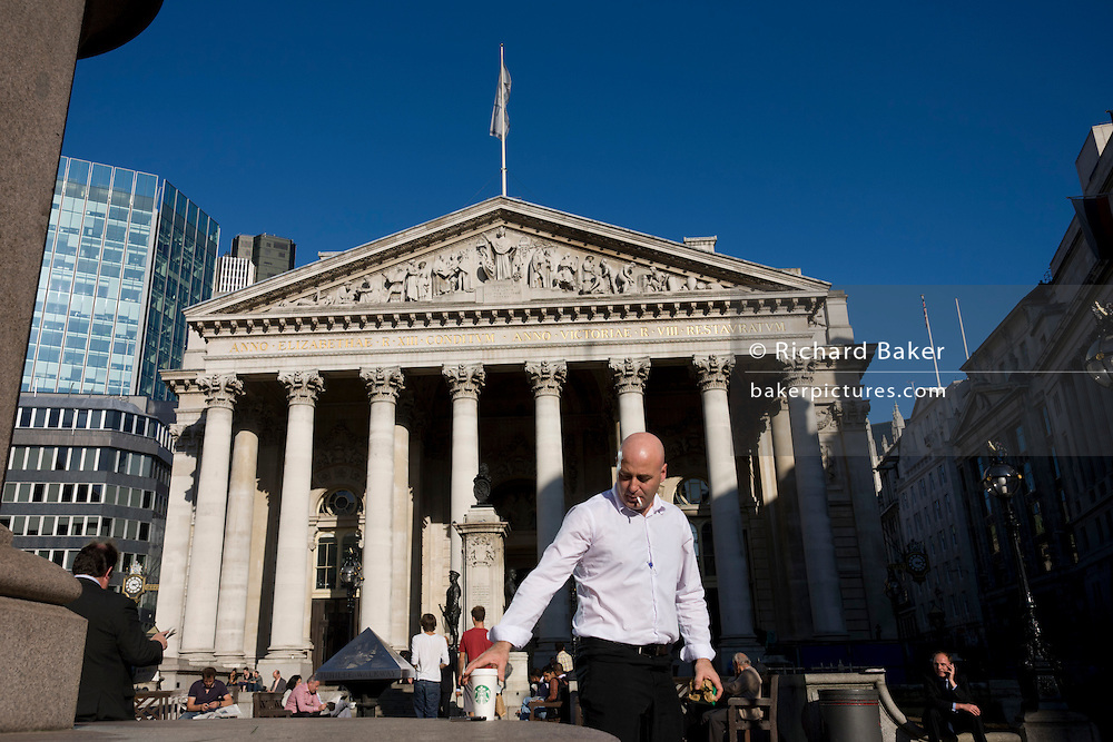 A businessman beneath the Romanesque columns of the Royal Excahnge in Bank triangle in the City of London. The tall and solid Corinthian pillars of the 3rd Royal Exchange built in 1842 by Sir William Tite. Looking upwards towards a memorial that commemorates the dead from the First World War of 1914-18 between the converging pillars of the Cornhill Exchange building and beyond, to the famous Bank of England in the City Of London, the financial district, otherwise known as the Square Mile.
