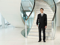 Confident Businessman holding folder standing in front of stairs