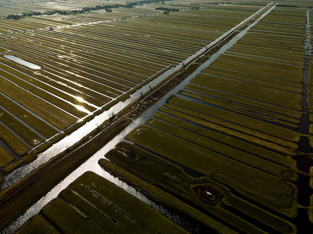 Nederland, Zuid-Holland, Gemeente Bergambacht, 20-02-2012; Krimpenerwaard met Polder Benedenkerk en Polder Zuidbroek. Kenmerkend voor de inrichting van de polder zijn de regelmatig gevormde ontginningsblokken, zogeheten cope-ontginningen. Het water in het midden is de Ringsloot (Slingerkade), gegraven rond 1800 in het kader van de voorbereiding van het afgraven van veen. Door de tegenvallend kwaliteit van het veen is de veenderij echter gestaakt..Krimpenerwaard with Polder Benedenkerk. Characteristic for the 'design' of the polder are the regularly shaped reclamation blocks, known as cope reclamations. The water in the middle is the Ringsloot (ring ditch), excavated in 1800 in preparation for the excavation of peat. Because of the disappointing quality of the peat bog, however, the was discontinued..luchtfoto (toeslag), aerial photo (additional fee required);.copyright foto/photo Siebe Swart.