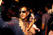 A clubber  with heavy facial piercings and a plastic doll at Bedrock at Heaven, London, 2000's