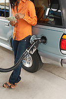 Woman leaning on van with fuel pump counting money, low section