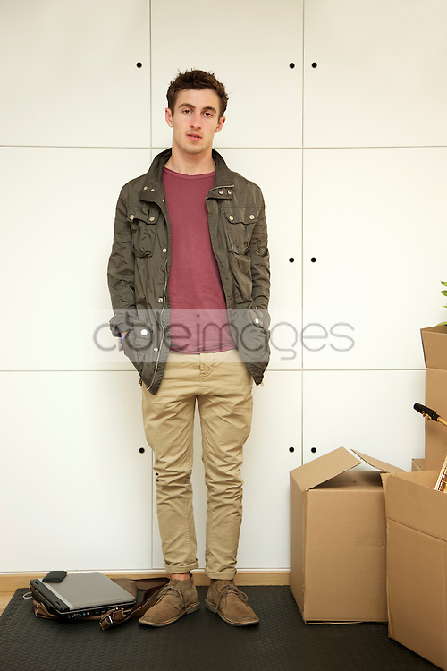 Man Standing with Hands in Pockets by Cardboard Boxes