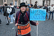 """A supporter of LGBT associations holds a placard reading """" Lesbians against Racism""""  and another placard reading  """"uterus rent free"""".<br /> Rally in central Rome of LGBT associations, for call for more rights for homosexual couples, the protest  after approval of the bill on civil union  which was approved recently by  the Italian Senate. Rome, Italy 5th March 2016"""