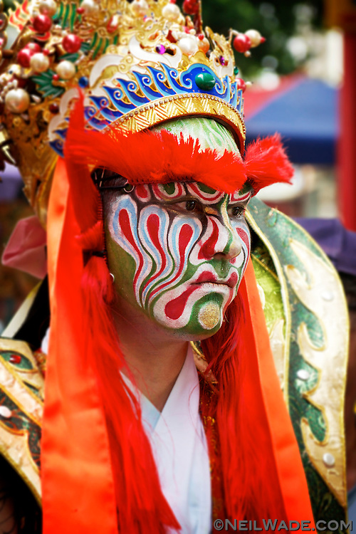 A dancer with the painted face of a Taoist God, said to be possessed by the spirit of that God, dances at a religious ceremony in Tainan, Taiwan.
