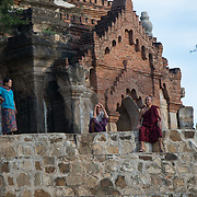 BAGAN, Myanmar (Burma) - Some locals watch the sunset from the waterfront of a pagoda in Bagan, Myanmar. The Ayeyarwaddy River (or Irrawaddy River) is the largest river in Myanmar. Running from north to south through the country it serves as a major transportation waterway and an important commercial path.